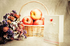 Apples in basket and wild flowers Stock Photo