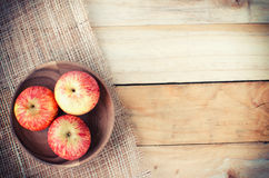 Apples in basket on wooden table Royalty Free Stock Photography