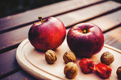 Apples on a board. Apples, walnuts and physalis on a board Royalty Free Stock Photography