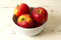 Apples in a bowl. Four red apples inside a white bowl that is resting on a white rustic coloured kitchen table. Apples are healthy and an excellent source of stock image