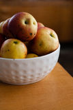 Apples in a bowl on the table. Apples in a white bowl on the table royalty free stock photography