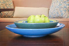 Apples in a bowl on a wooden table in a living room Royalty Free Stock Photos