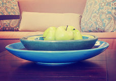 Apples in a bowl on wooden table in a living room toned with a Stock Photos