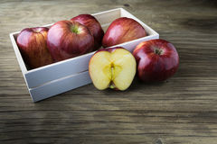 Apples in the box. Red apples on a wooden table. Stock Photo