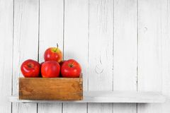 Apples in a box on wooden shelf. Royalty Free Stock Photography