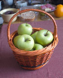 Apples in brown wicker basket on kitchen desk Royalty Free Stock Image