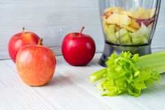 Apples, a bunch of celery, and a food processor on white table. Concept of healthy nutrition Stock Photos