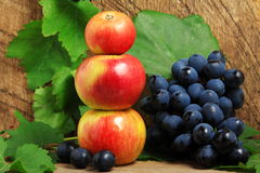 Apples and bunch of grapes. Three apples and bunch of grapes on wooden background Stock Images