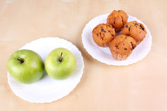 Apples and cakes on white plates Royalty Free Stock Photo