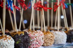 Apples in caramel and sprinkles. Sweet delicious dessert on a stick royalty free stock images