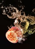 Apples carved in water splash. Handcarved red apple dropped in a water tank royalty free stock photography