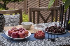 Apples, cherries and currants on table on the terrace of house. Real photo. Concept stock image