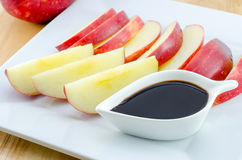 Apples with chocolate on wooden table Stock Images