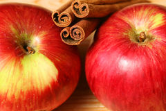 Apples and cinnamon. Sticks - closeup of the red juicy fruits Stock Photography