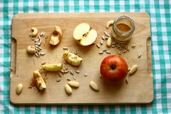 Apples with cinnamon and nuts. Healthy breakfast or snack - pieces of red organic apple, almonds, cashew nuts and sunflower seeds on wood and green tablecloth Stock Images