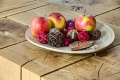 Apples in clay plate on wooden table. Stock Image