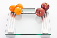 Apples and clementines on scales,close up Royalty Free Stock Photos