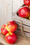 Apples in crate. Fresh red organic apples in wooden crate on table Stock Photography