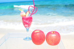 Apples and drink on the beach Stock Photography