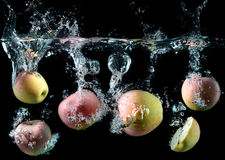 Apples droping in to the clear water Royalty Free Stock Photography