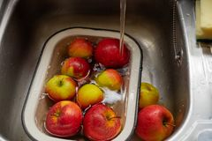 Apples in an enamel bowl under the flow water from tap in the sink stock image