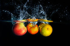 Apples falling and splashing into clear water Stock Image