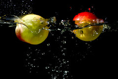Apples falling to the water Stock Photography