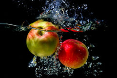 Apples falling to the water Stock Photos