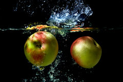 Apples falling to the water Stock Images