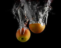 Apples falling into the water Stock Photography
