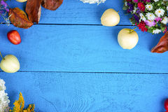 Apples, flowers, plums and leaf litters on wooden background Royalty Free Stock Images