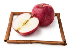Apples in a frame from sticks of cinnamon isolated Stock Photo