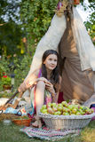 Apples in the garden. Portrait of Teenage girl siting on the ground in front of summer tent royalty free stock image