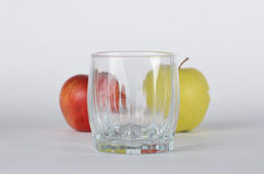 Apples with glass. Red and green apless behind empty glass on the white background Royalty Free Stock Photography