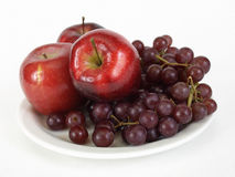 Apples and Grapes. Three red apples and a bunch of red seedless grapes on a white plate. Over a white background Royalty Free Stock Images