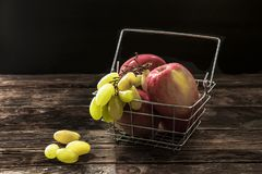 Apples and grapes in a basket. Stock Image