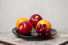 Apples with grapes and oranges. On black plate Royalty Free Stock Photography