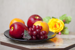 Apples with grapes and oranges in the black plate. And on table Stock Photos