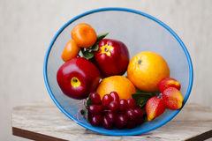 Apples with grapes and oranges in the sieve. And on table Royalty Free Stock Photos
