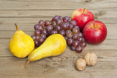 Apples grapes and pears, wooden table Royalty Free Stock Photos
