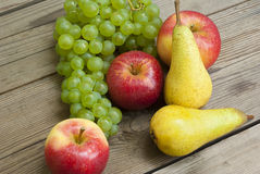 Apples grapes and pears, wooden table Royalty Free Stock Photography