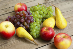 Apples grapes and pears, wooden table Stock Images