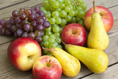 Apples grapes and pears, wooden table Royalty Free Stock Image
