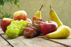 Apples grapes and pears, wooden table Royalty Free Stock Images