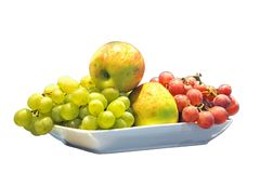 Apples, and  grapes on a plate,  on the white. Apples, green and red grapes on a plate, isolated on the white Royalty Free Stock Image