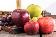 Apples and grapes on wooden background in domestic composition Stock Photos