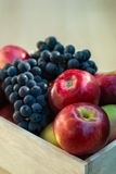 Apples and grapes in a wooden box, close up. Selective focus Stock Image
