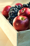 Apples and grapes in a wooden box, close up, selective focus. Red apples and grapes in a wooden box, close up, selective focus Royalty Free Stock Images