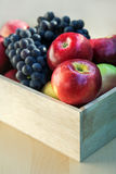 Apples and grapes in a wooden box, close up, selective focus. Red apples and grapes in a wooden box, close up, selective focus Royalty Free Stock Photo