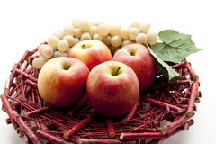 Apples and grapes on wooden plate Royalty Free Stock Images
